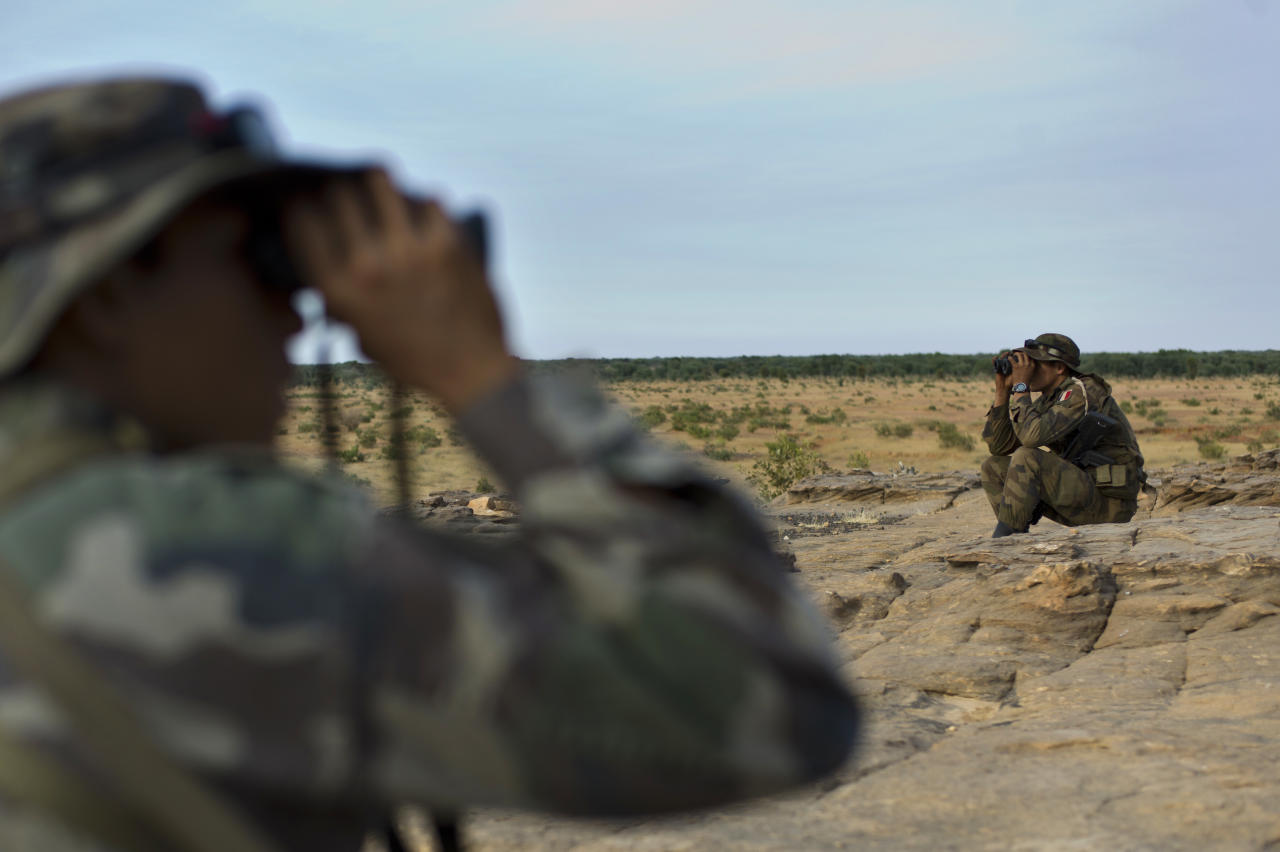 French soldiers look with binoculars in the outskirts of Sevare, Mali, some 620 kms (385 miles) north of Bamako, Wednesday, Jan. 23, 2013. The U.S. airlift of French forces to Mali to fight Islamic extremists is expected to go on for another two weeks, Pentagon officials said, as hundreds of African troops from Nigeria, Togo, Burkina Faso and Senegal are now joining the French-led intervention. (AP Photo/Thibault Camus)