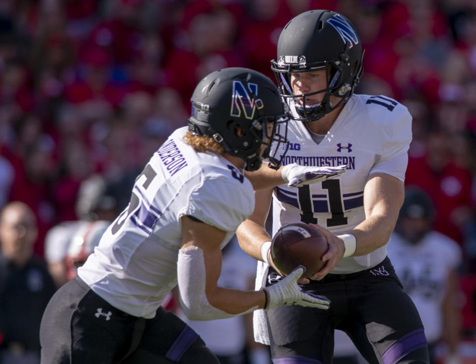 Northwestern quarterback Aidan Smith (11) hands off the ball to running back Drake Anderson (6) during an NCAA college football game against Nebraska, Saturday, Oct. 5, 2019 in Lincoln, Neb. (Emily Haney/Lincoln Journal Star via AP)