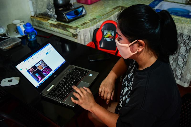 FILE PHOTO: Lorraine Ann Imperio browses her computer as she prepares to barter goods online in Las Pinas City, Philippines. (Photo by MARIA TAN/AFP via Getty Images)