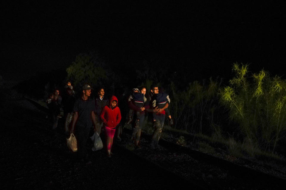 Emely, 8, of Honduras, center, walks with a group of migrants after turning themselves in upon crossing the U.S.-Mexico border Wednesday, May 12, 2021, in La Joya, Texas. Growing numbers of migrant families are making the heart-wrenching decision to separate from their children and send them into the U.S. alone. (AP Photo/Gregory Bull)