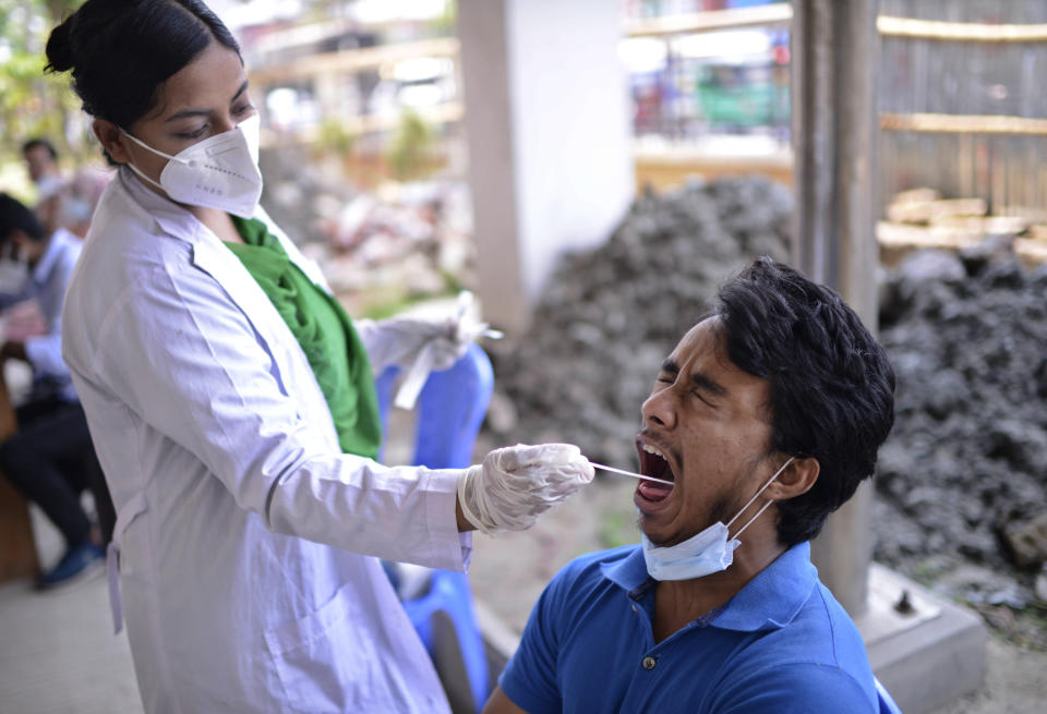 A Bangladeshi health worker takes a mouth swab sample of a man to test for COVID-19 in Dhaka, Bangladesh, Saturday, May 8, 2021. India's surge in coronavirus cases is having a dangerous effect on neighboring Bangladesh. Health experts warn of imminent vaccine shortages just as the country should be stepping up its vaccination drive, and as more contagious virus variants are beginning to be detected. (AP Photo/Mahmud Hossain Opu)