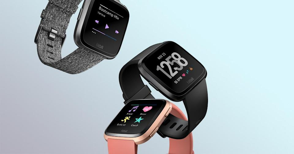 Three Fitbit Versa smartwatches displayed in black, gray, and pink.