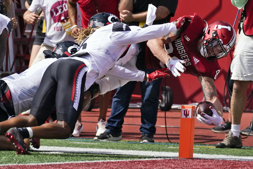 Indiana's Peyton Hendershot (86) dives over the goal line for a touchdown against Cincinnati's Bryan Cook (6) during the first half of an NCAA college football game, Saturday, Sept. 18, 2021, in Bloomington, Ind. (AP Photo/Darron Cummings)