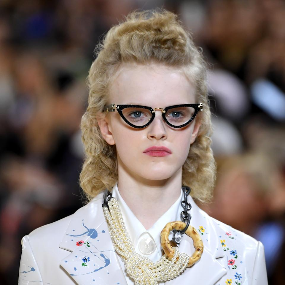 """At Miu Miu, Miuccia Prada sent models down the runway wearing off-the-shoulder cardigans, embellished vests, and plenty of leather skirts covered in playful floral prints. To complement the fashion, Redken global creative director Guido Palau made an equally strong statement with the hair, creating distinct curl for most models. """"I've done a tissue-set, '40s-inspired look,"""" he explained. """"It's an old-school way of achieving curls, where you wrap individual sections of hair with a tissue, heat them up with an iron, then allow them to cool. Once you take out the tissues, the result is a soft curl. I've then brushed through and shaped the curls into a '40s style at the front, and squared-off in the back."""" Paired with cat-eye glasses, the hair also had a very librarian geek-chic vibe. His key product to create the look was <a href=""""https://www.ulta.com/triple-dry-15-dry-texture-finishing-spray?productId=xlsImpprod18851278"""" rel=""""nofollow"""">Redken Triple Dry 15 Dry Texturizing Spray</a> for lots of chunky texture throughout."""