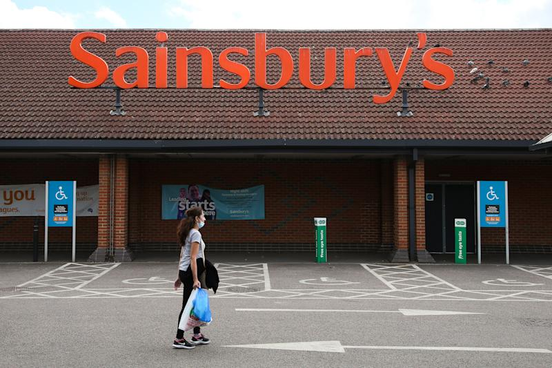 A woman wearing a face mask walks past a Sainsbury's supermarket in north London. (Photo by Dinendra Haria/SOPA Images/LightRocket via Getty Images)