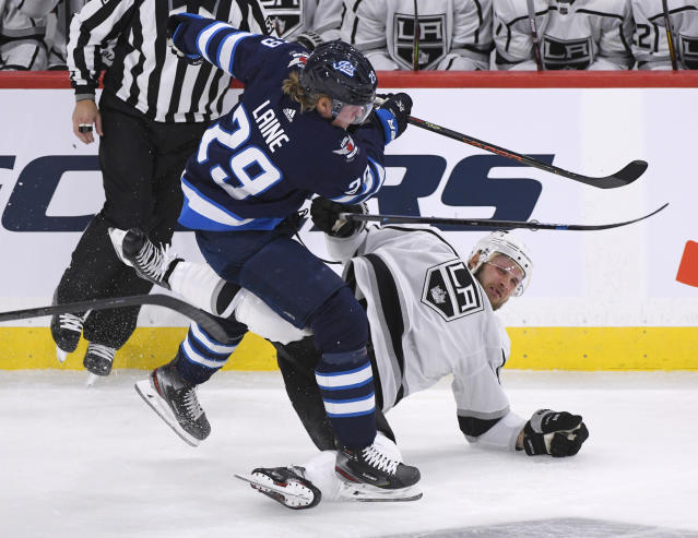 Winnipeg Jets' Patrik Laine (29) checks Los Angeles Kings' Kyle Clifford during the first period of an NHL hockey game Tuesday, Oct. 22, 2019, in Winnipeg, Manitoba. (Fred Greenslade/The Canadian Press via AP)