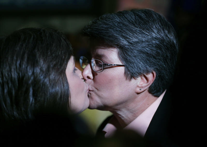 Cindy Meneghin, right, kisses her partner Maureen Kilian, both from Butler, N.J., during a rally at Garden State Equality in Montclair, N.J., hours after a Superior Court Judge ruled that New Jersey is unconstitutionally denying federal benefits to gay couples and must allow them to marry, Friday, Sept. 27, 2013. Meneghin has been with Kilian for 39 years. Judge Mary Jacobson ruled it legal for gay couples to marry in the state beginning Oct. 21, 2013. The ruling comes after a group of gay marriage supporters sued the state in July, days after the U.S. Supreme Court struck down key parts of a law that blocked the federal government from granting benefits to gay couples. (AP Photo/Julio Cortez)