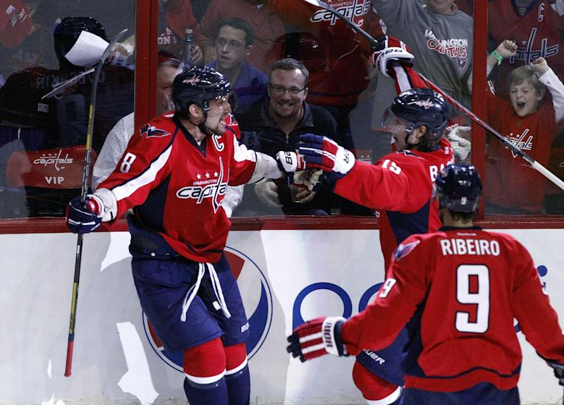 Washington Capitals left wing Alex Ovechkin (8), from Russia, celebrates his goal with center Nicklas Backstrom (19), from Sweden, and center Mike Ribeiro (9) in the second period of Game 1 of a Stanley Cup NHL hockey playoff series against the New York Rangers, Thursday, May 2, 2013, in Washington. The Capitals won 3-1. (AP Photo/Mark Tenally)