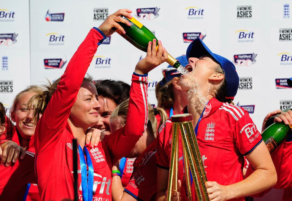 England captain Charlotte Edwards (R) is given champagne by Danielle Wyatt after the Women's Ashes Series third NatWest T20 between England Women and Australia Women at Emirates Durham ICG on August 31, 2013 in Chester-le-Street, England.  (Photo by Stu Forster/Getty Images)