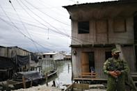 Security forces guard the Nayero bridge in La Playita where 2,000 Afro-Colombian inhabitants live in fear for their lives