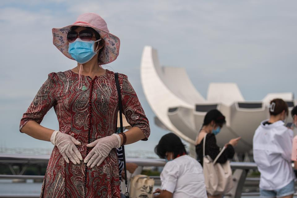A woman wearing 2 masks and gloves at Singapore's Marina Bay on Sunday, 1st August 2021 in SIngapore. Community cases have risen steadily as the largest Covid-19 cluster that began in Singapore's main fishing port weeks ago has since reported more than 1000 cases linked to it yesterday. (Photo by Joseph Nair/NurPhoto via Getty Images)