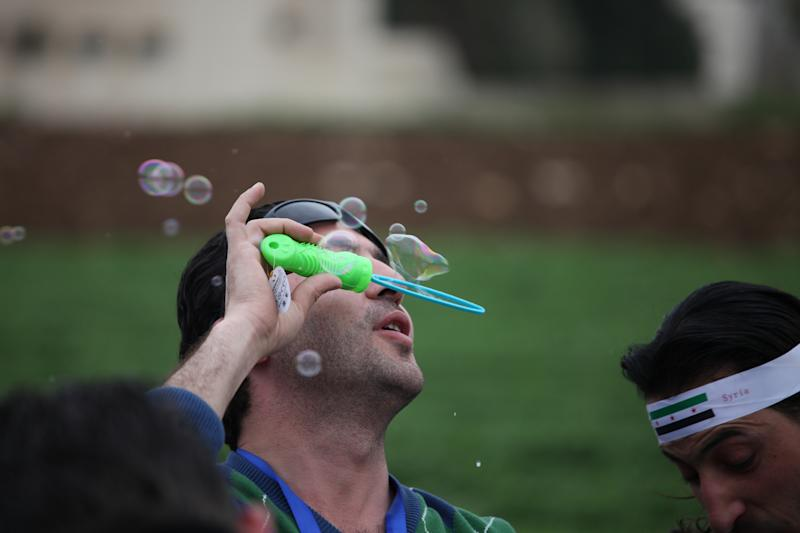 Syrian protester blows bubbles during a celebration to commemorate the second anniversary of the Syrian revolution, in Amman, Jordan, Friday, March 15, 2013. Around a thousand Syrians gathered in front of the Syrian embassy, and chanted slogans against Assad, and the Baath regime that has ruled Syria for the last 40 years. (AP Photo/Mohammad Hannon)