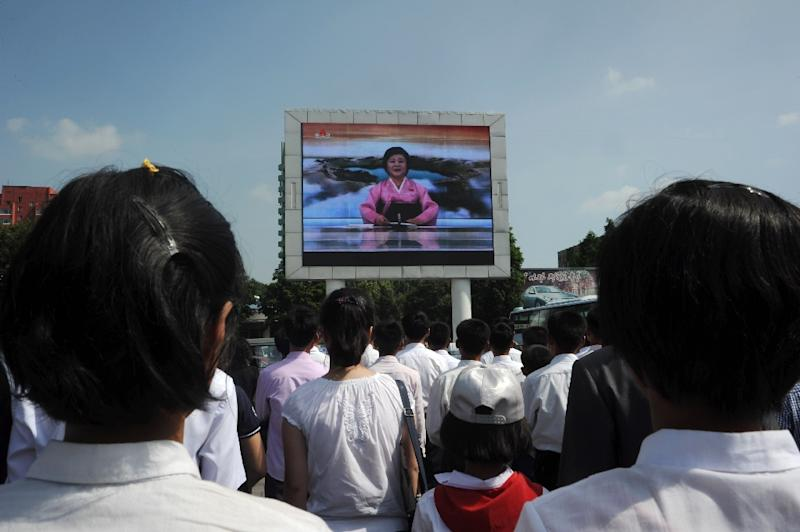 "Pyongyang residents watch TV announcer Ri Chun-Hee speak about the successful launch of the intercontinental ballistic missile ""Hwasong-14"" on a big screen near the Pyongyang Railway Station in Pyongyang on July 4, 2017 (AFP Photo/Kim Won-Jin)"