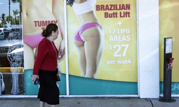 A window display advertises low-cost cosmetic procedures outside a surgery clinic in Miami. (AP Photo/Ellis Rua)
