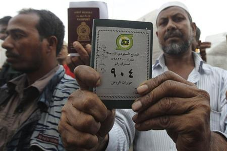 Foreign workers displays his passport as he waits outside a labour office in Riyadh