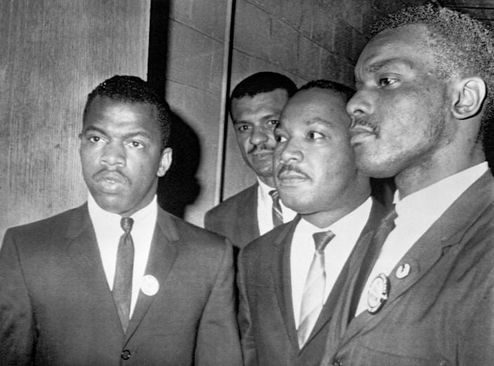 Reverend Martin Luther King Jr., (center) is escorted into a mass meeting at Fisk University in Nashville. His colleagues are, left to right, John Lewis, national chairman of the Student Non-Violent Committee and Lester McKinnie, on of the leaders in the racial demonstrations in Nashville recently. King gave the main address to a packed crowd. (Photo by Bettmann Archive/Getty Images) (Photo: Bettmann via Getty Images)
