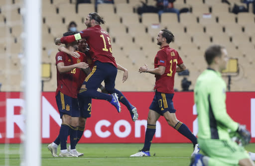 Spain's captain Sergio Ramos, center, celebrates with scorer Ferran Torres, left, during the UEFA Nations League soccer match between Spain and Germany in Seville, Spain, Tuesday, Nov. 17, 2020. (AP Photo/Miguel Morenatti)