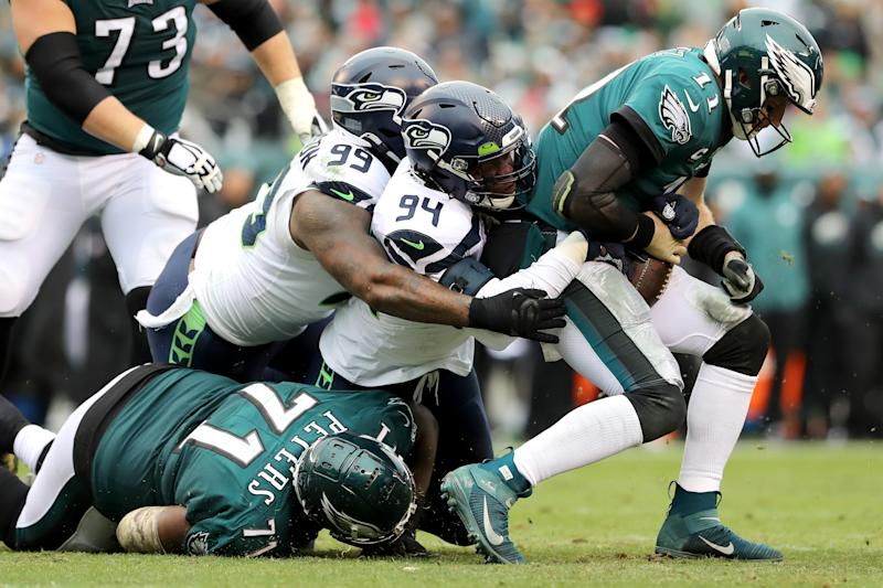 PHILADELPHIA, PENNSYLVANIA - NOVEMBER 24: Quinton Jefferson #99 and Ezekiel Ansah #94 of the Seattle Seahawks sack quarterback Carson Wentz #11 of the Philadelphia Eagles in the first half at Lincoln Financial Field on November 24, 2019 in Philadelphia, Pennsylvania. (Photo by Elsa/Getty Images)