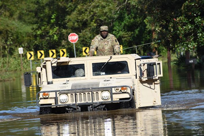 Personnel from the Louisiana National Guard drive through flooded streets in Alexandria, Louisiana, on Saturday.