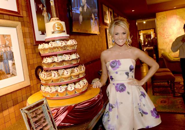 NASHVILLE, TN - JUNE 07: Carrie Underwood poses with commemorative cupcakes created by Ivey Childers of Ivey Cake in celebration of her 5th anniversary at The Grand Ole Opry on June 7, 2013 in Nashville, Tennessee. (Photo by Rick Diamond/Getty Images)