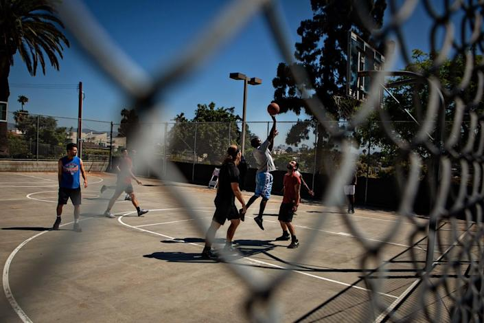 A pickup basketball game seen through a chain-link fence