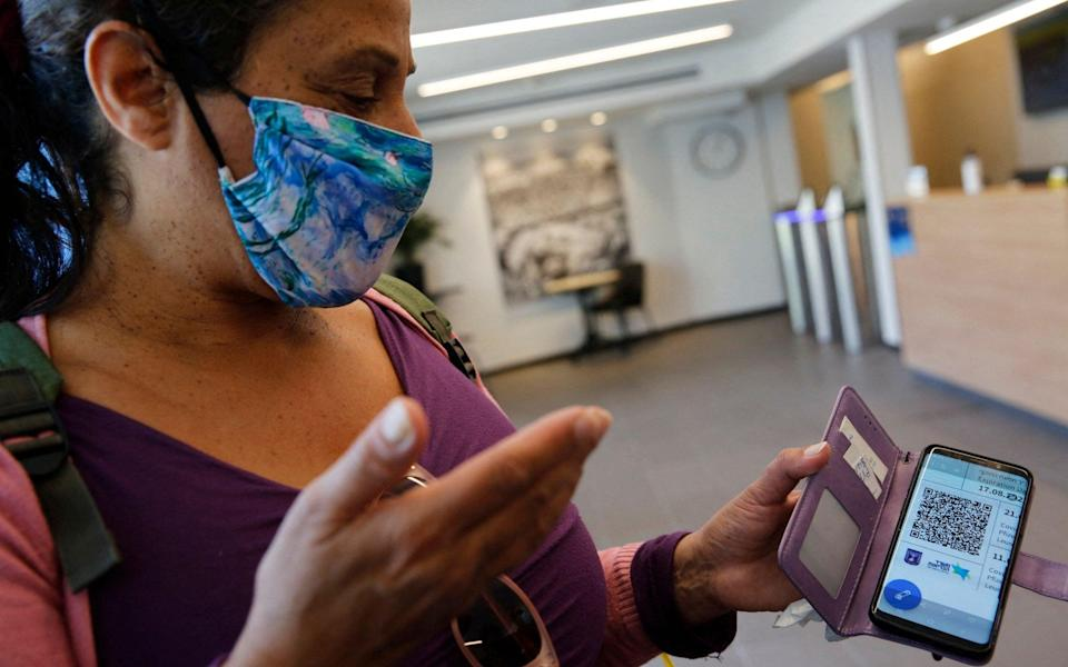 A woman shows her 'green pass', providing proof that she has been fully vaccinated against Covid, before she enters a gym in the Israeli city of Tel Aviv - Gil Cohen-Magen/AFP