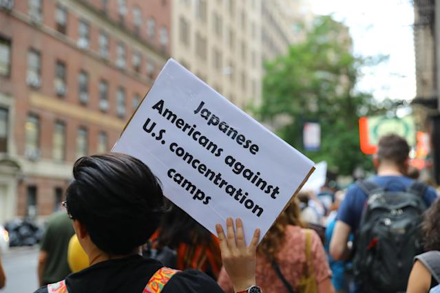 "<p>A protester holds up a sign that reads ""Japanese Americans against U.S. concetration camps"" while marching toward the United Nations in New York City on June 20, 2018. (Photo: Gordon Donovan/Yahoo News) </p>"
