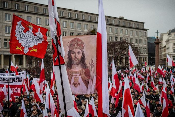 A picture of Jesus is seen amid Polish flags during a massive demonstration of supporters of the Law and Justice (PiS) right wing opposition party in Warsaw, on December 13, 2014 (AFP Photo/Wojtek Radwanski)