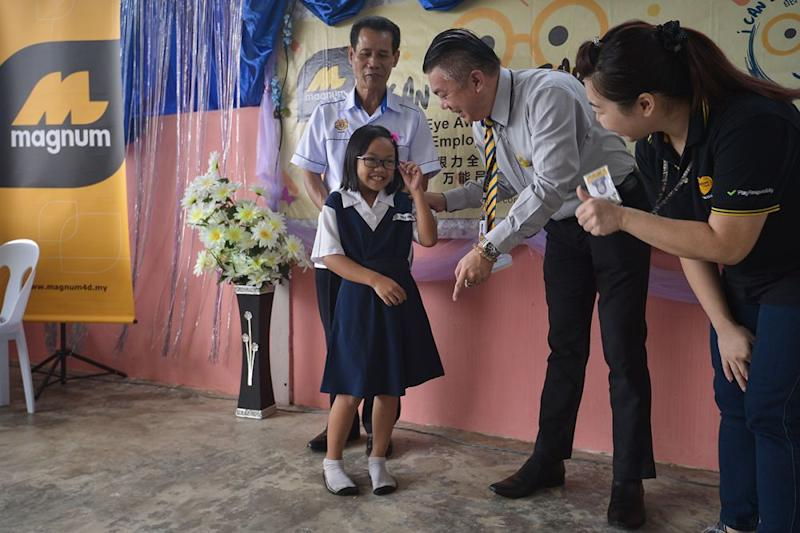 Magnum Regional Manager Liew Kee Chuan (second right) presents the pair of spectacles to a student during the 'I Can See Clearly Now' Spectacles Presentation & Eye Awareness Talk at SK Atas Singai in Kuching August 29, 2018. ― Pictures by Mukhriz Hazim