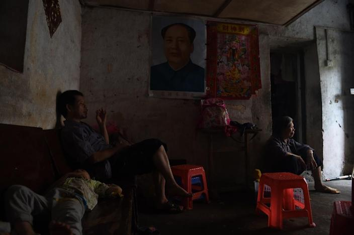 A family in their house with a portrait of late communist leader Mao Zedong in the old town of Wuxuan, in south China's Guangxi province (AFP Photo/Greg Baker)