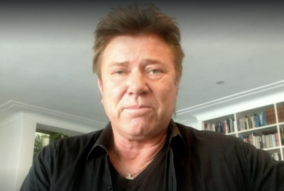 Richard Wilkins in a black top in his Sydney home