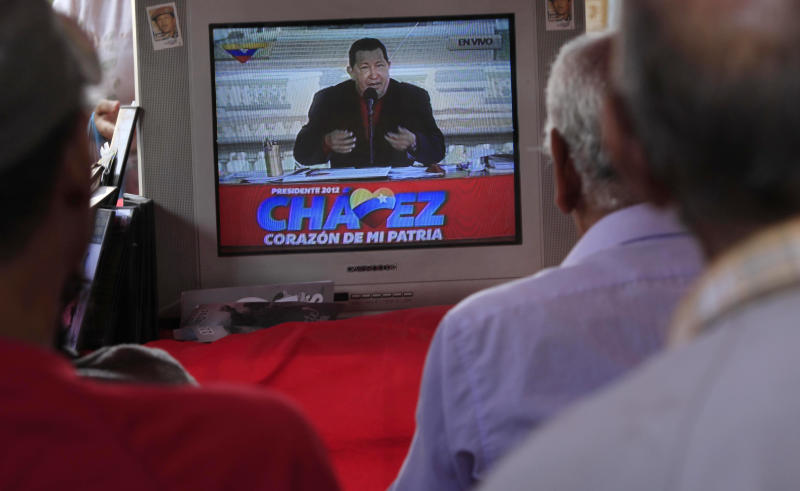 In this Sept. 5, 2012 photo, people watch a TV in Caracas, Venezuela broadcasting President Hugo Chavez delivering a speech as presidential candidate. Nearly 14 years after President Hugo Chavez took office, and despite the biggest oil bonanza in Venezuela's history, there's little outward sign of the nearly one trillion petrodollars that have flowed into the country. The populist president has used the oil wealth to buttress his support through cash handouts, state-run grocery stores and a gamut of other social programs. With more money in the economy, incomes are higher and the number of people living in poverty has fallen. Yet some experts say Chavez could have done much more to improve the country's infrastructure, boost its economy and invest in the very oil industry that keeps Venezuela afloat. (AP Photo/Ariana Cubillos)