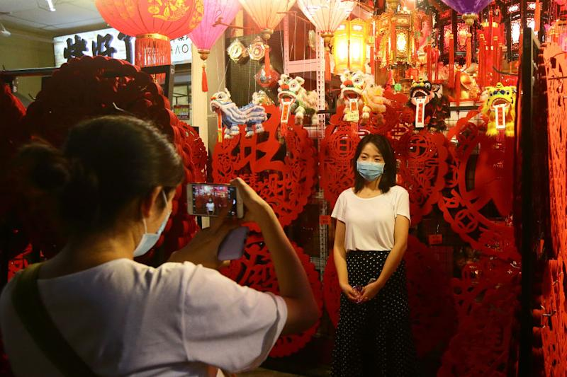 SINGAPORE - JANUARY 24: Shoppers wear mask as they take photo with a lunar new year decoration at Chinatown on January 24, 2020 in Singapore. Singapore confirmed another two cases of the Wuhan viruses today, making a total of three, as Singapore prepares to usher in the Year of the Rat, one of the most anticipated holidays on the Chinese calendar. Also known as the Spring festival or the Lunar New Year, the celebrations last for about 15 days. (Photo by Suhaimi Abdullah/Getty Images)