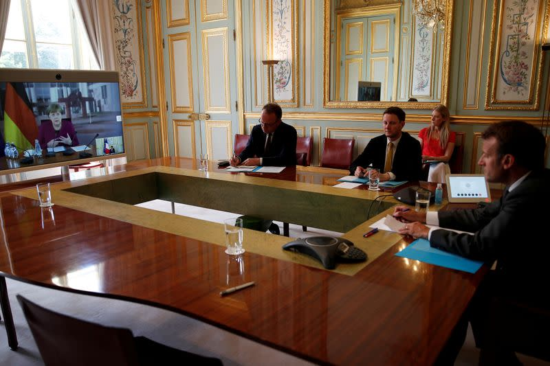 FILE PHOTO: French President Emmanuel Macron listens to German Chancellor Angela Merkel during a video conference at the Elysee Palace