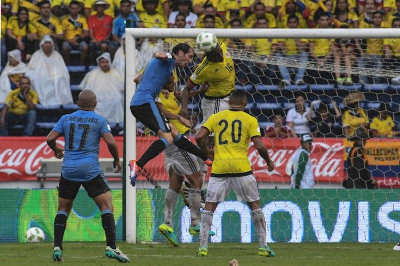 Uruguay's Diego Godin (2nd L) and Colombia's defender Yerry Mina (2nd R) jump for a header during their Russia 2018 FIFA World Cup qualifier football match in Barranquilla, Colombia, on October 11, 2016
