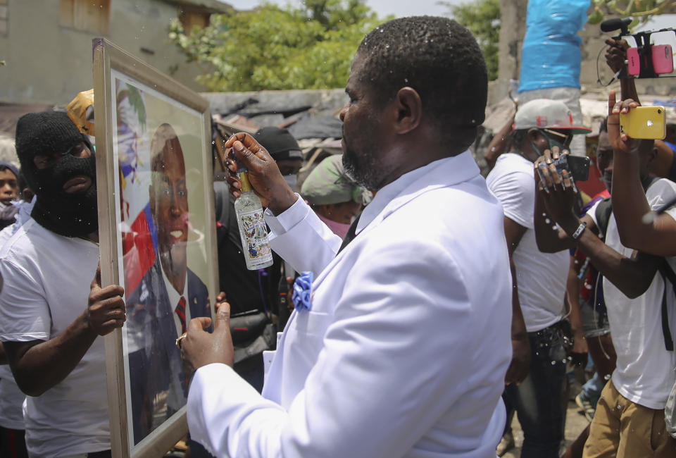 """Jimmy Cherizier, alias Barbecue, a former police officer who heads a gang coalition known as """"G9 Family and Allies,"""" blesses an image of slain Haitian President Jovenel Moise during a rally to demand justice in Lower Delmas, a district of Port-au- Prince, Haiti Monday, July 26, 2021. Moise was assassinated on July 7 at his home. (AP Photo/Joseph Odelyn)"""