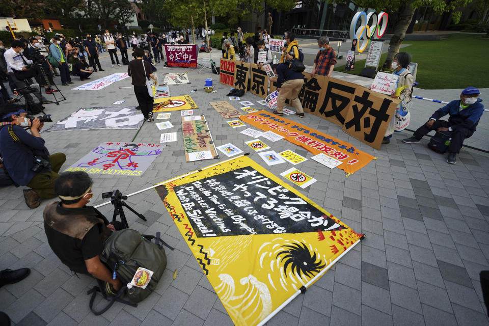 """People against the Tokyo 2020 Olympics set to open in July, protest around Tokyo's National Stadium during the anti-Olympics demonstration Sunday, May 9, 2021. The banner in the background reads: """"Oppose Tokyo Olympics."""" (AP Photo/Eugene Hoshiko)"""