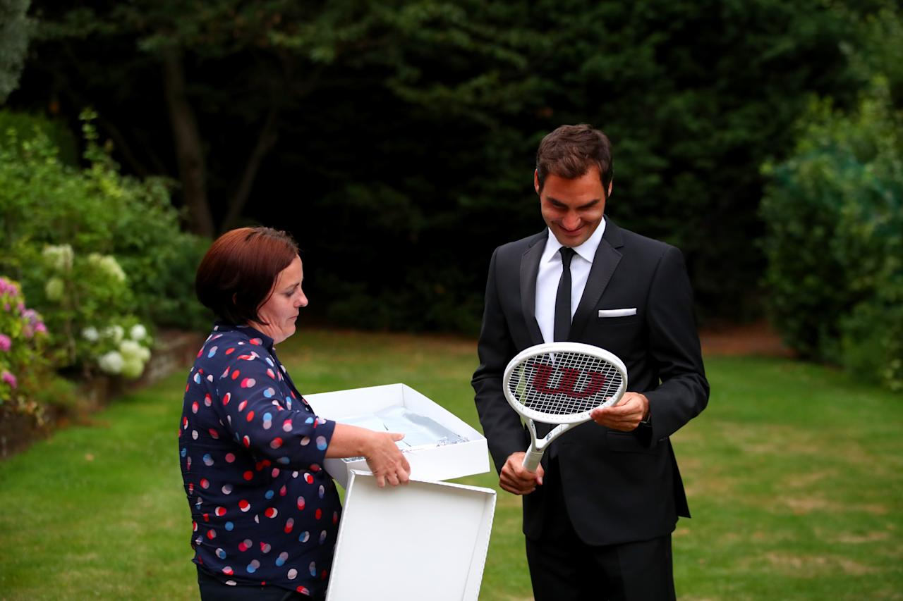 "LONDON, ENGLAND - JULY 16:  Roger Federer of Switzerland celebrates his Wimbledon record with an exclusive commemorative ""8"" Wilson tennis racket next to Joanne Thomas Kemp after his victory against Marin Cilic of Croatia on day thirteen of the Wimbledon Lawn Tennis Championships at the All England Lawn Tennis and Croquet Club on July 16, 2017 in London, England.  (Photo by Clive Brunskill/Getty Images for Wilson)"