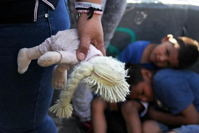 A Mexican woman holds a doll next to children at the Paso Del Norte Port of Entry, in the US-Mexico border in Chihuahua state, Mexico (AFP Photo/HERIKA MARTINEZ)