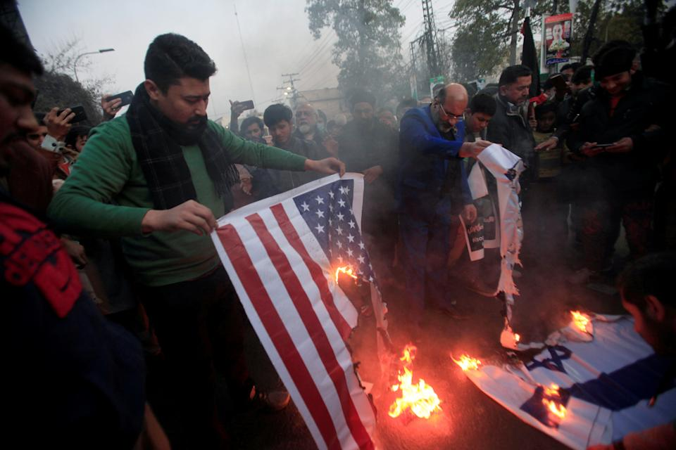 Pakistani Shi'ite Muslim supporters of Majlis-e-Wahdat-e-Muslimeen (MWM) burn U.S and Israel's flags to condemn the death of Iranian Major-General Qassem Soleimani, who was killed in an airstrike near Baghdad, during a protest in Lahore, Pakistan January 3, 2020. (Mohsin Raza/Reuters)