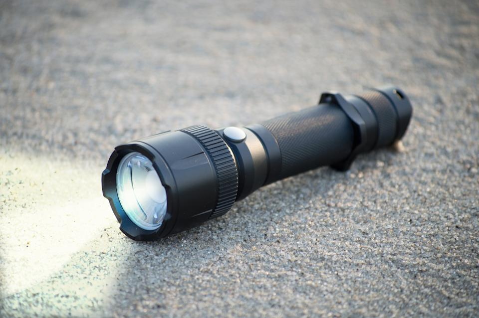 pocket LED flashlight lies on a sand. Lantern for tourism and daily use EDC