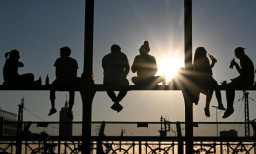 People have a drink and watch the sunset after a warm spring day in Munich, Germany