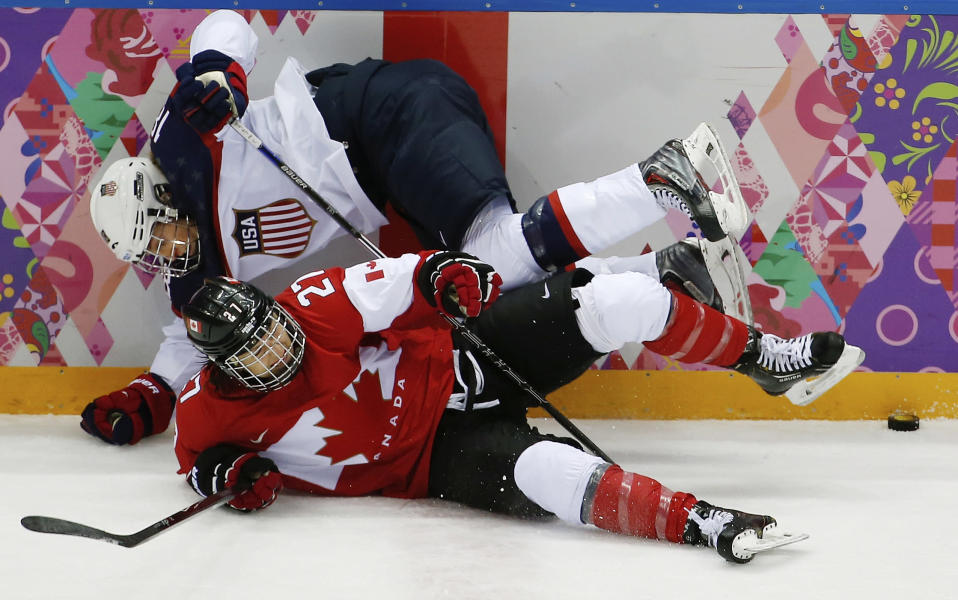 Kelli Stack of the United States (16) collides with Haley Irwin of Canada (21) during the first period of the women's gold medal ice hockey game at the 2014 Winter Olympics, Thursday, Feb. 20, 2014, in Sochi, Russia. (AP Photo/Julio Cortez)