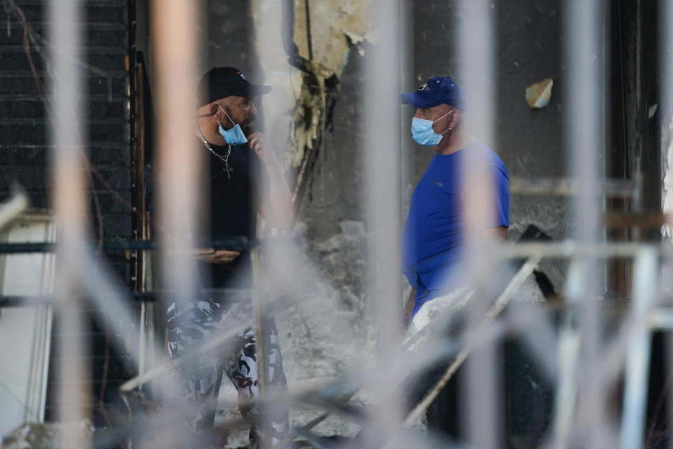 Vasken Samuelian, owner of Men's Suit Outlet, and Janik Kayajian, the manager, survey damages inside the burned store building, Monday, June 1, 2020, in Long Beach after overnight protests over the death of George Floyd died in police custody on May 25 in Minneapolis. (AP Photo/Ashley Landis)