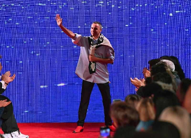 586309ba Belgian fashion designer Raf Simons waves to his guests, on the runway  during New York