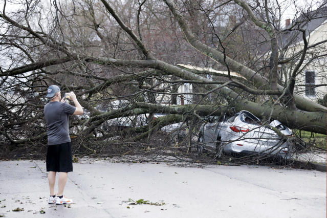 A resident photographs damage after a tornado touched down Tuesday, March 3, 2020, in Nashville, Tenn. (AP Photo/Mark Humphrey)