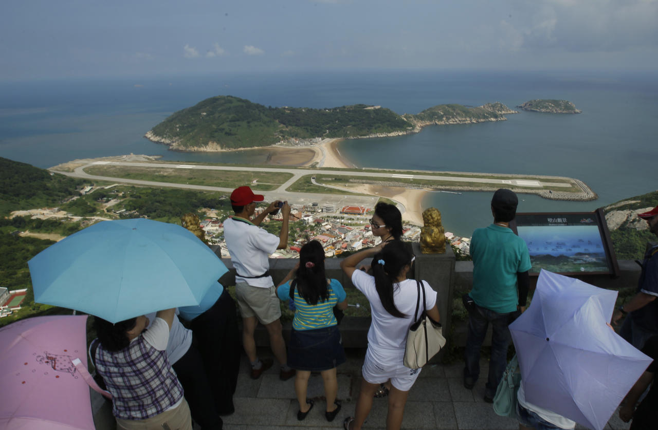 In this Aug. 20, 2012 photo, from the 220-meter (670 feet) summit of Mt. Bi, visitors look down on the airport's single runway jutting out into into the sea on Beigan in the Matsu island group, off northern Taiwan. In early July some 3,000 Matsu residents voted 57 to 43 to permit casino gambling. Their votes were clearly influenced by the promises of not only a casino, but also a tourist resort, expanded airport, roadway infrastructure, a university, and perhaps most alluring of all, a monthly payment of 80,000 New Taiwan dollars ($2,666) for every resident. (AP Photo/Wally Santana)