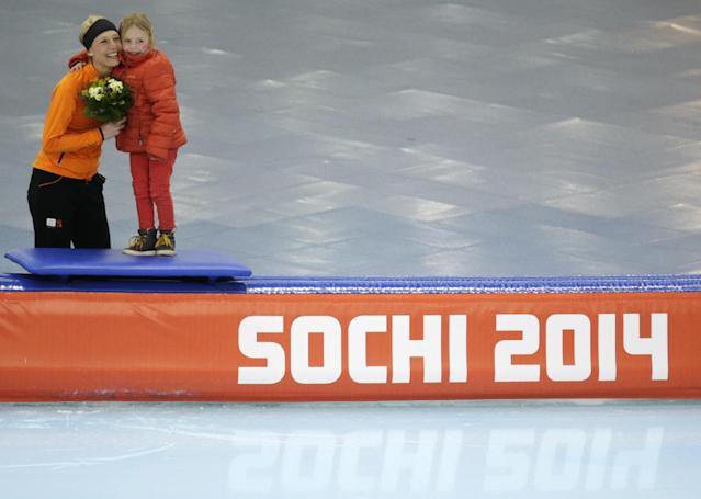 Bronze medallist Carien Kleibeuker of the Netherlands hugs her daughter Annemijn as they pose for photographers during the flower ceremony for the women's 5,000-meter speedskating race at the Adler Arena Skating Center during the 2014 Winter Olympics in Sochi, Russia, Wednesday, Feb. 19, 2014. (AP Photo/Matt Dunham)