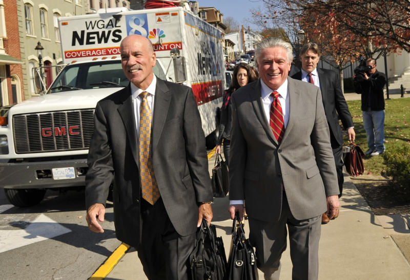 Attorneys for the NCAA Everett Johnson, left, and Tom Scott, right, exit the Centre County Courthouse, Tuesday, Oct. 29, 2013, in Bellefonte, Pa., after a court hearing. Lawyers for the NCAA, the Paterno family and Paterno supporters were at the Centre County Courthouse, Tuesday for a court hearing on whether to allow a lawsuit filed against the NCAA by the family of longtime Penn State football coach Joe Paterno and others to go forward. The lawsuit brought by the Paterno family aims to wipe out the NCAA sanctions against Penn State University. (AP Photo/Centre Daily Times, Nabil K. Mark) MAGS OUT MANDATORY CREDIT