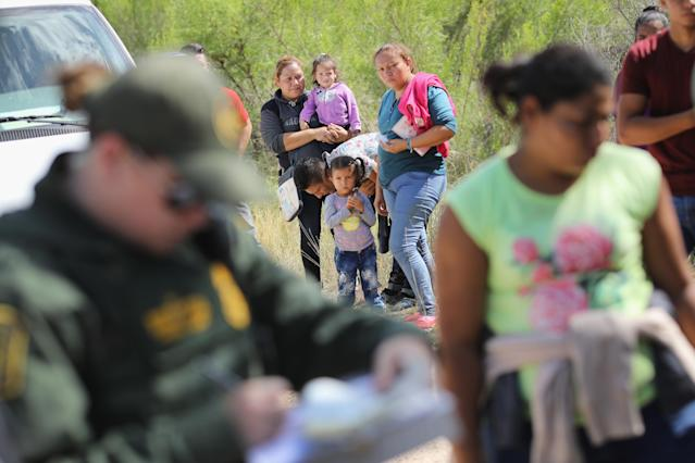 <p>Central American asylum seekers wait as U.S. Border Patrol agents take them into custody on June 12, 2018 near McAllen, Texas. The families were then sent to a U.S. Customs and Border Protection (CBP) processing center for possible separation. (Photo: John Moore/Getty Images) </p>